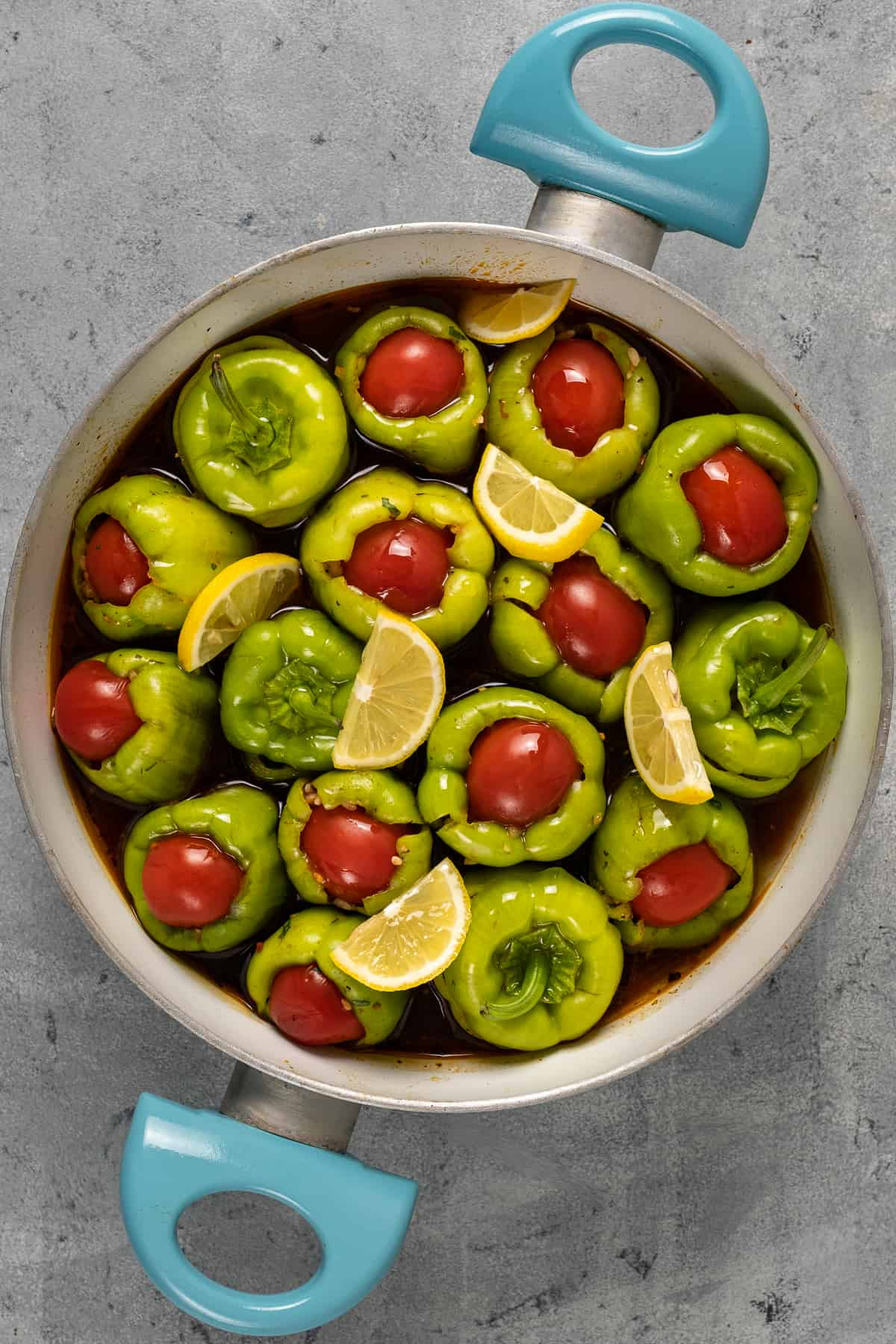 Turkish green peppers stuffed with a rice filling, topped with halved cherry tomatoes and garnished with lemon slices in a pan.