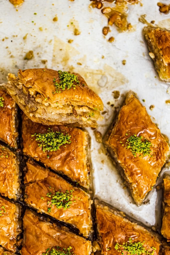 Walnut baklava slices topped with crumbled pistachio in a pan.