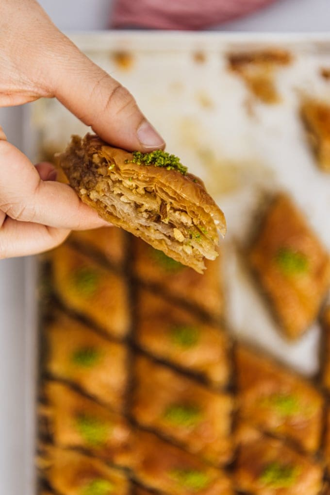 Woman holding a slice of homemade baklava with walnuts and pistachio