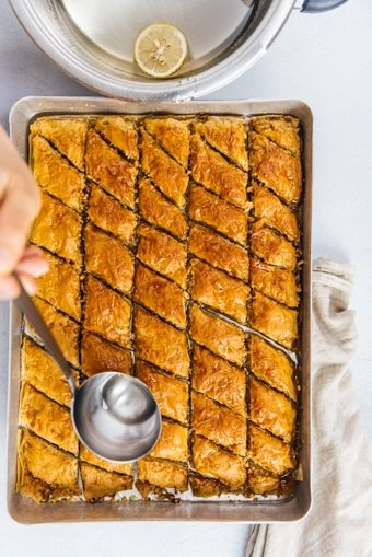 Pouring baklava syrup with a ladle over newly baked baklava