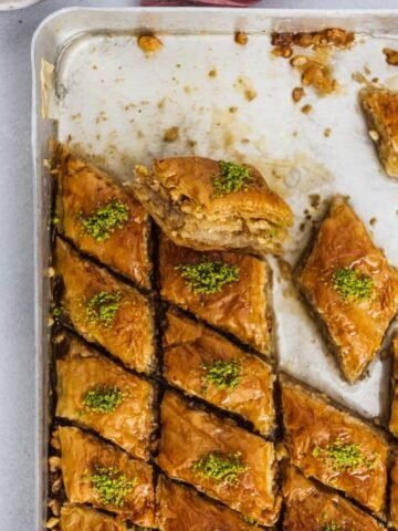 Newly baked Turkish baklava dessert filled with walnuts and topped with pistachio in a baking sheet