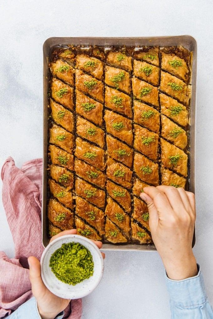 Sprinkling Turkish pistachios over Turkish baklava
