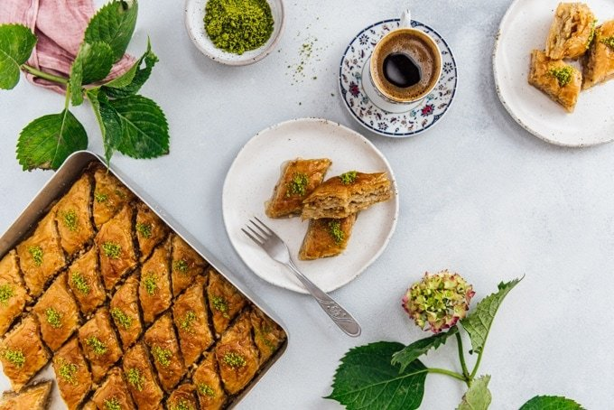 Turkish coffee in a traditional Turkish coffee cup, two slices of turkish baklava on a ceramic plate, a baking sheet full of newly made baklava