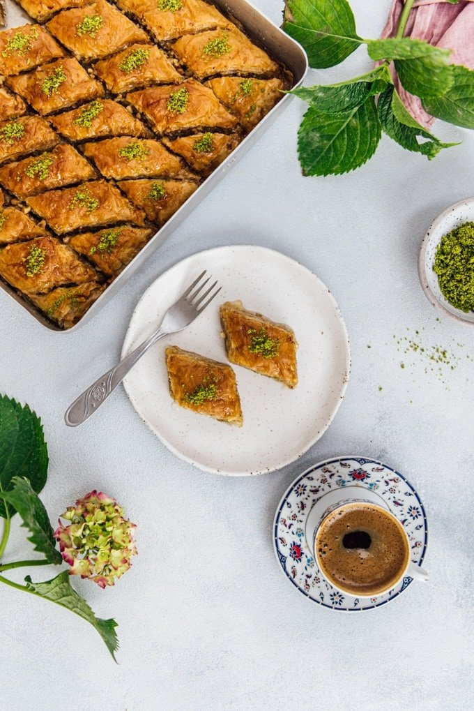 Turkish pastry baklava on a ceramic plate and in a traditional pan accompanied by Turkish coffee