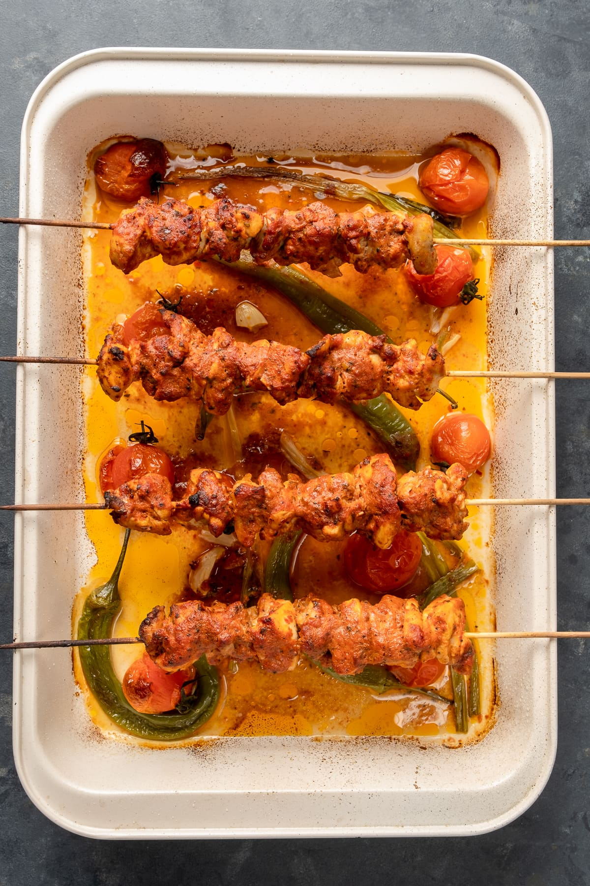 Chicken kabobs baked in oven on the edges of a rectangular baking pan, tomatoes, green peppers and green onions are in the pan.