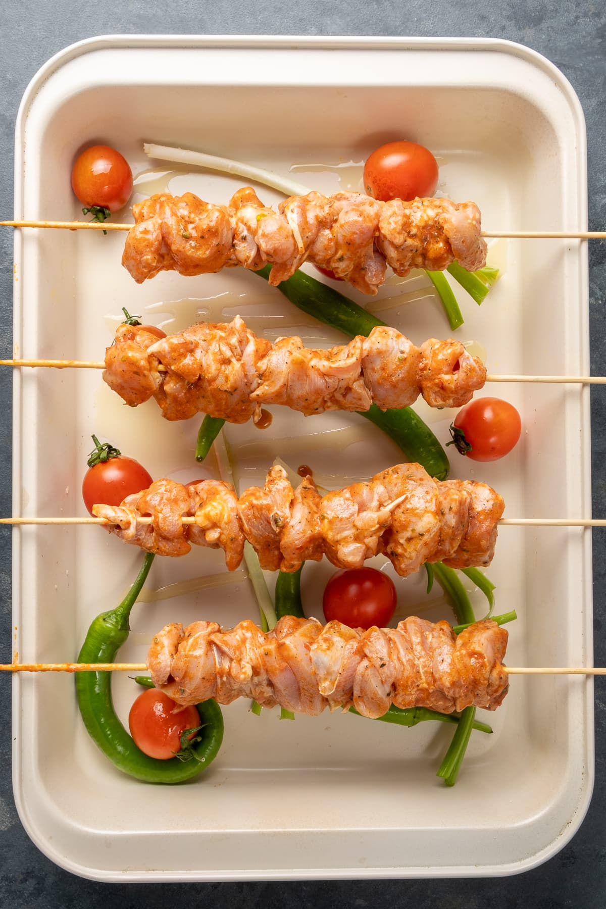 Raw chicken skewers placed on the edges of a baking pan and tomatoes, green peppers and green onions in the pan.