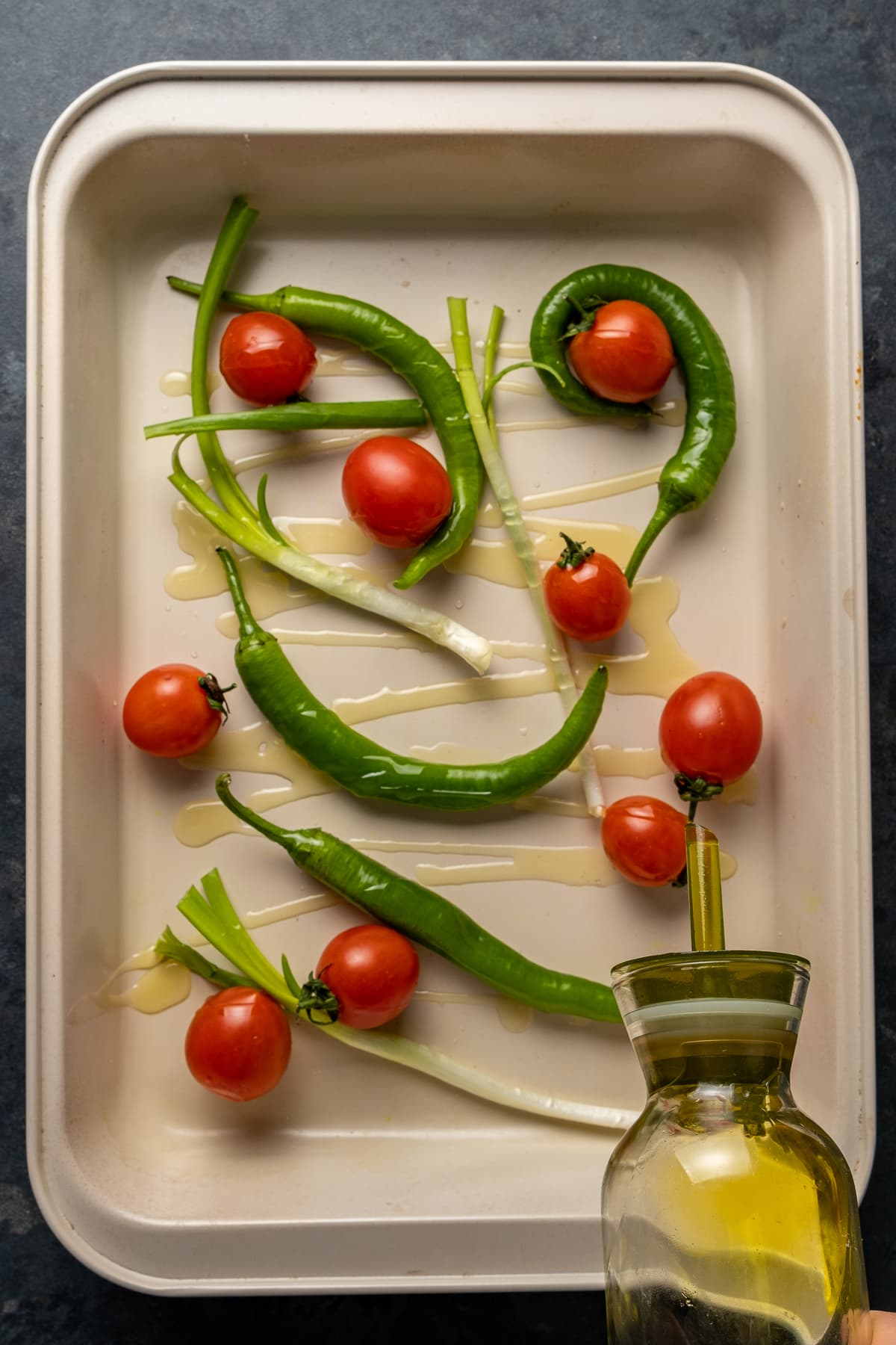 Drizzling olive oil from a bottle on tomatoes, green peppers and green onions in a baking pan.