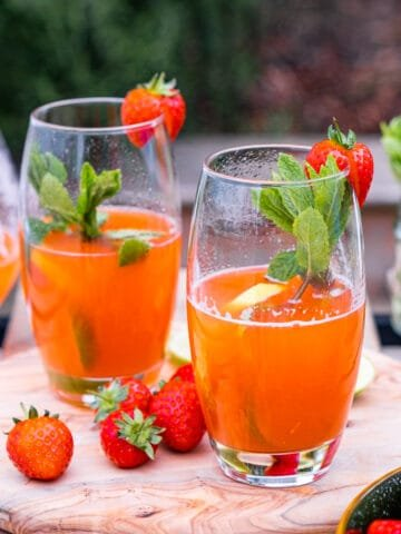 Strawberry lemonade in two tall glasses garnished with mint leaves and strawberries on a wooden board with an outside background.