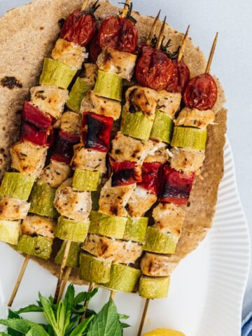 Spicy chicken kabobs with zucchinis, tomatoes and red bell peppers served on tortillas accompanied by herbs and lemon