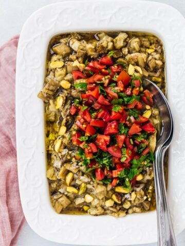 Turkish eggplant salad topped with pistachios, tomatoes and parsley in a white rectangular pan with spoons