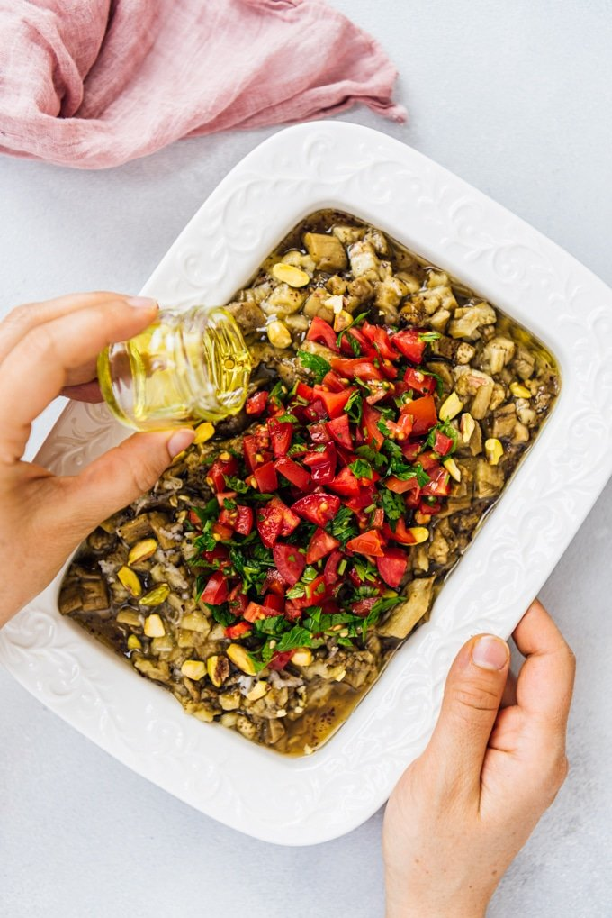Drizzling olive oil over roasted eggplant salad turkish