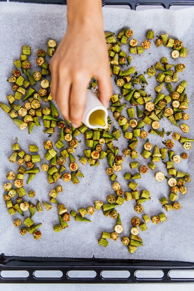 A hand drizzling olive oil over chopped and spiced okras on a baking sheet.