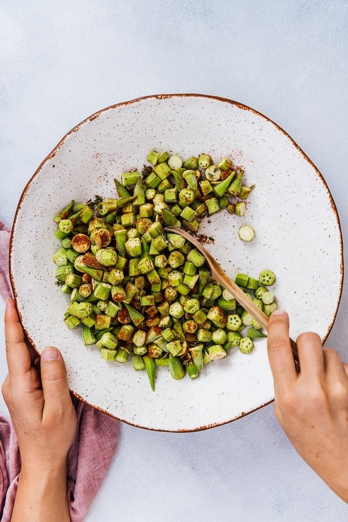 Hands stirring chopped okra and spices in a white ceramic bowl with a wooden spoon.