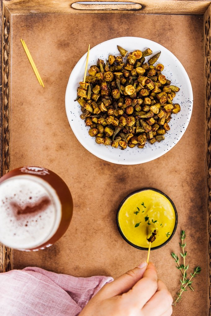 Roasted okra chips served with turmeric tahini dip and a glass of beer.