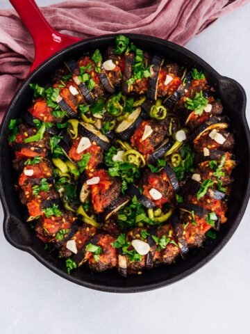Baked eggplant kebab with meatballs in cast iron skillet