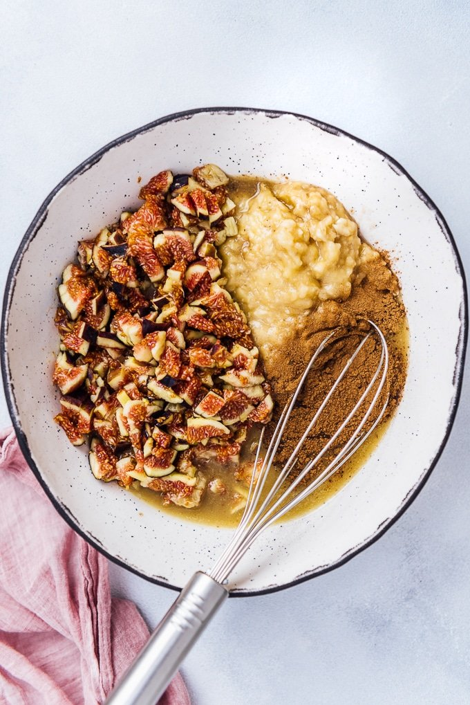 Fresh figs, mashed banana, cinnamon in a white ceramic bowl with a hand whisk in it.