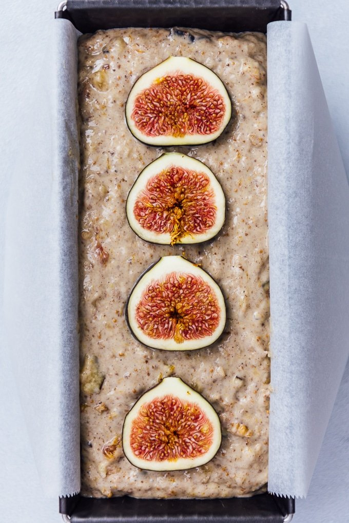 Banana fig loaf cake batter in a loaf pan topped with fresh fig slices.