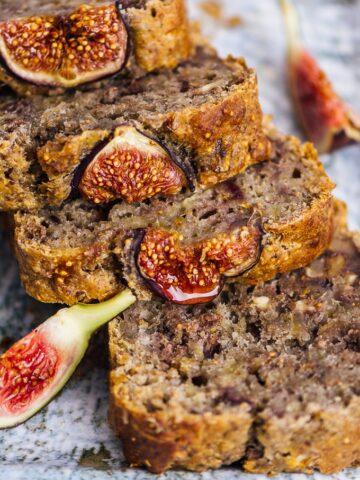 Vegan fresh fig bread with walnuts sliced on a ceramic plate.
