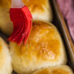 Soft homemade dinner rolls with a melted butter topping