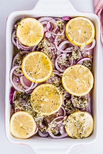 chicken thighs with lemon slices, onions and lemon sauce to be baked