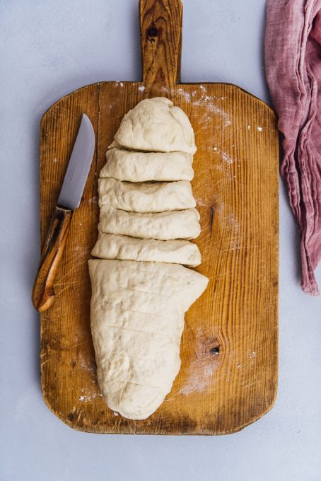 how to shape dinner rolls by cutting the dough on a wooden board