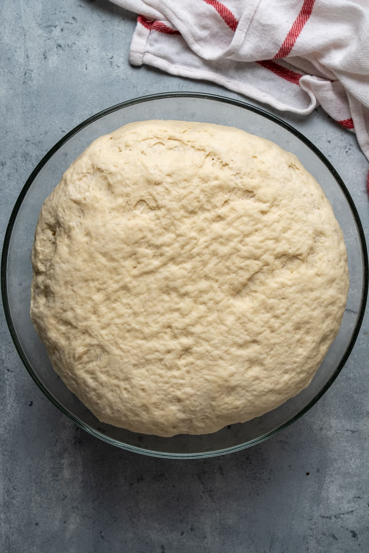 The dough doubled in size in a glass mixing bowl on a grey background.