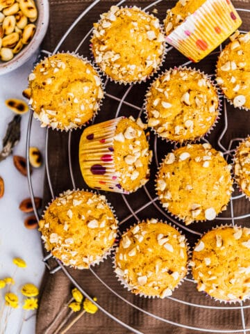 Pumpkin muffins with cake mix on a cooling rack and peanuts on the side.