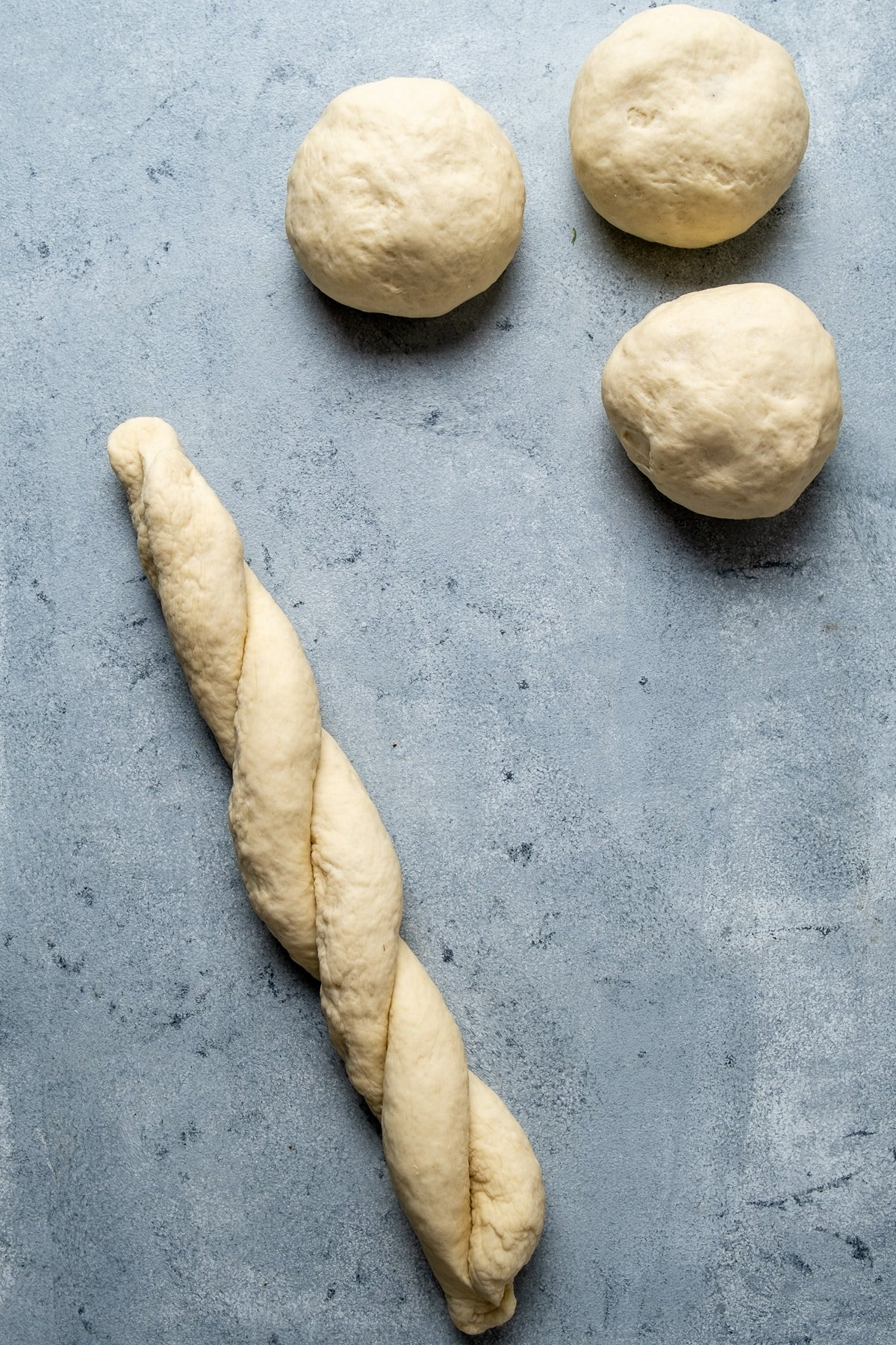 Braided strands of dough and more dough balls on a grey background.