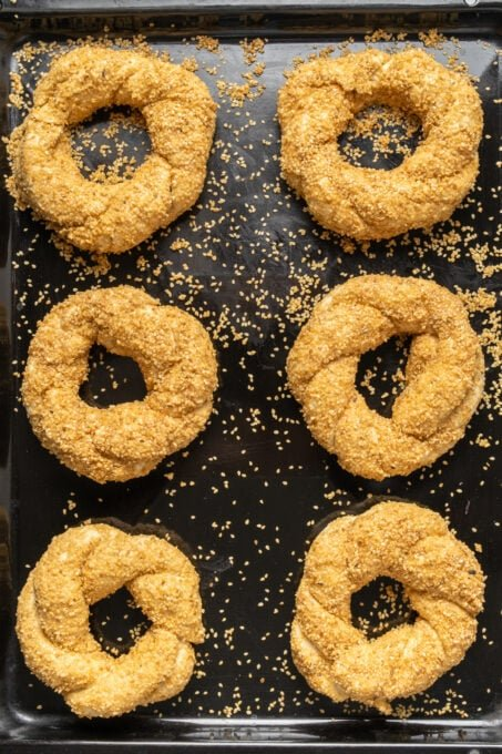 Breaded ring shaped simits coated with sesame seeds to be baked on a black baking sheet.