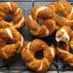 Golden colored, crunchy Turkish simits coated with toasted sesame seeds on a black cooling rack on a dark background.