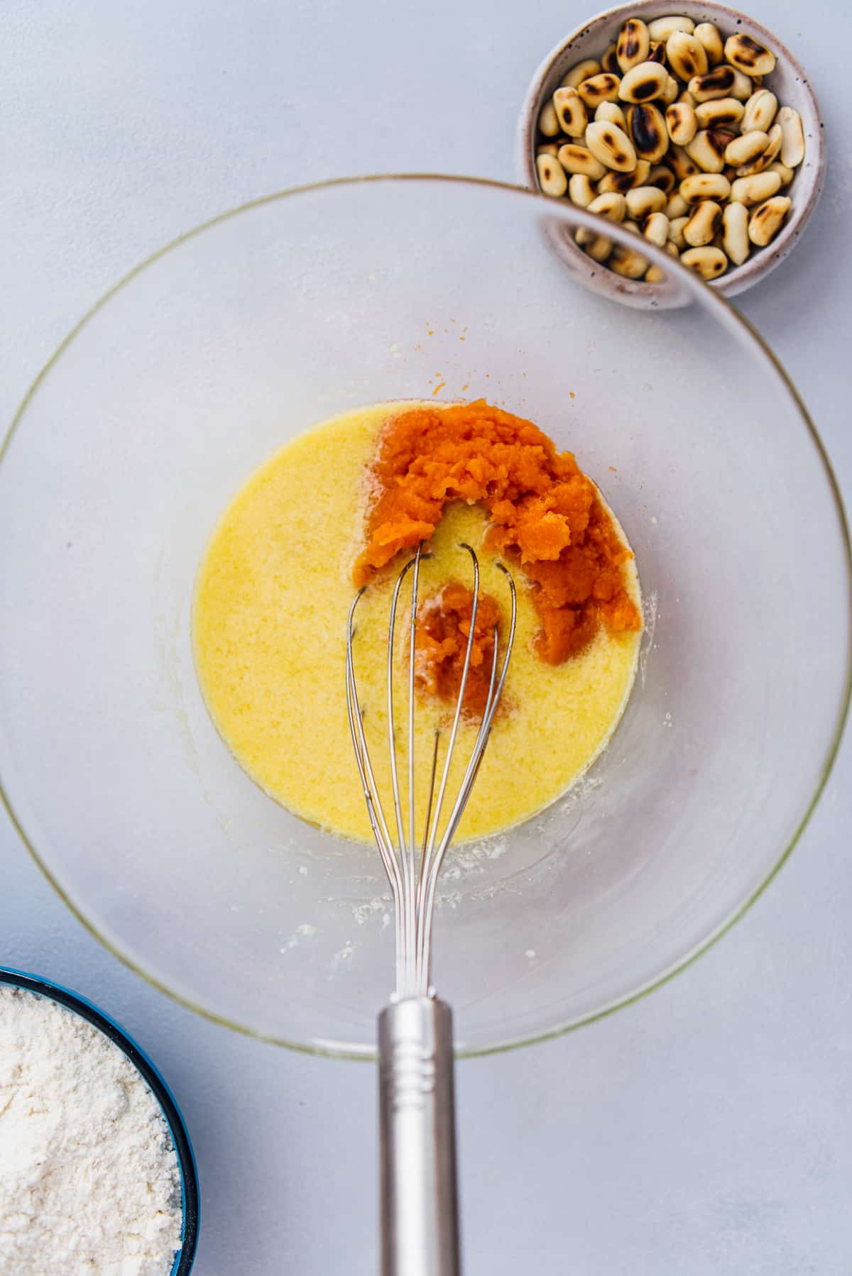 Eggs and pumpkin puree in a mixing bowl and a hand whisk inside it.