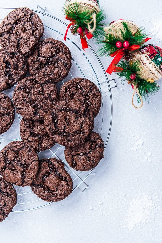Chocolate cake mix cookies on a cooling rack with Christmas decorations