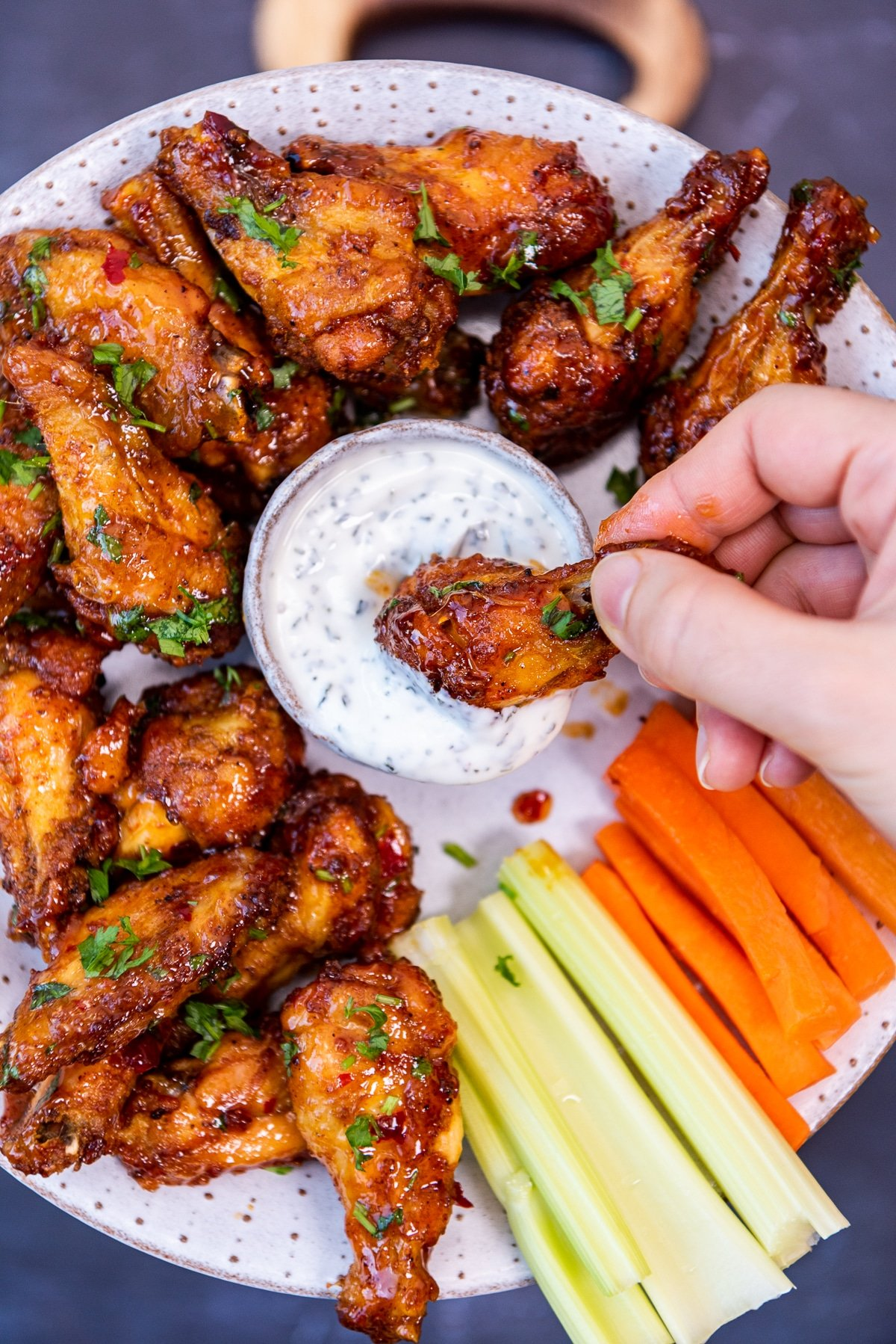 A hand dipping a spicy chicken wing into yogurt sauce and other chicken wings, carrot and celery sticks on the side.