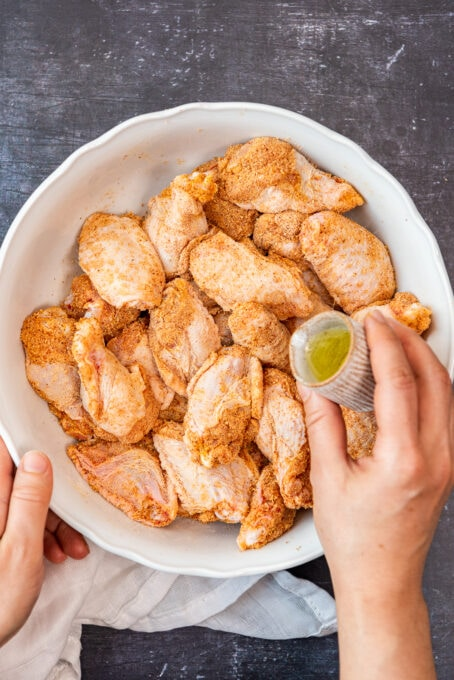 A hand drizzling olive oil over seasoned wings.