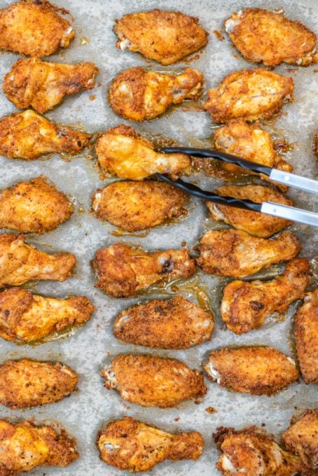 Flipping half baked wings on the baking sheet with tongs.