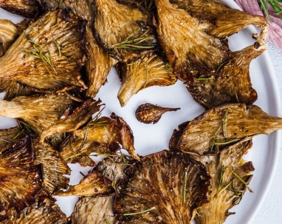Roasted oyster mushrooms with rosemary served on a white plate.