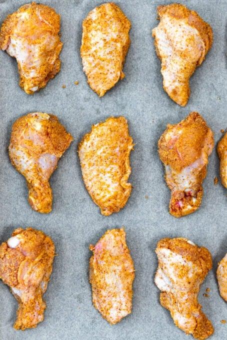 Seasoned chicken wings placed on a baking paper lined baking sheet.