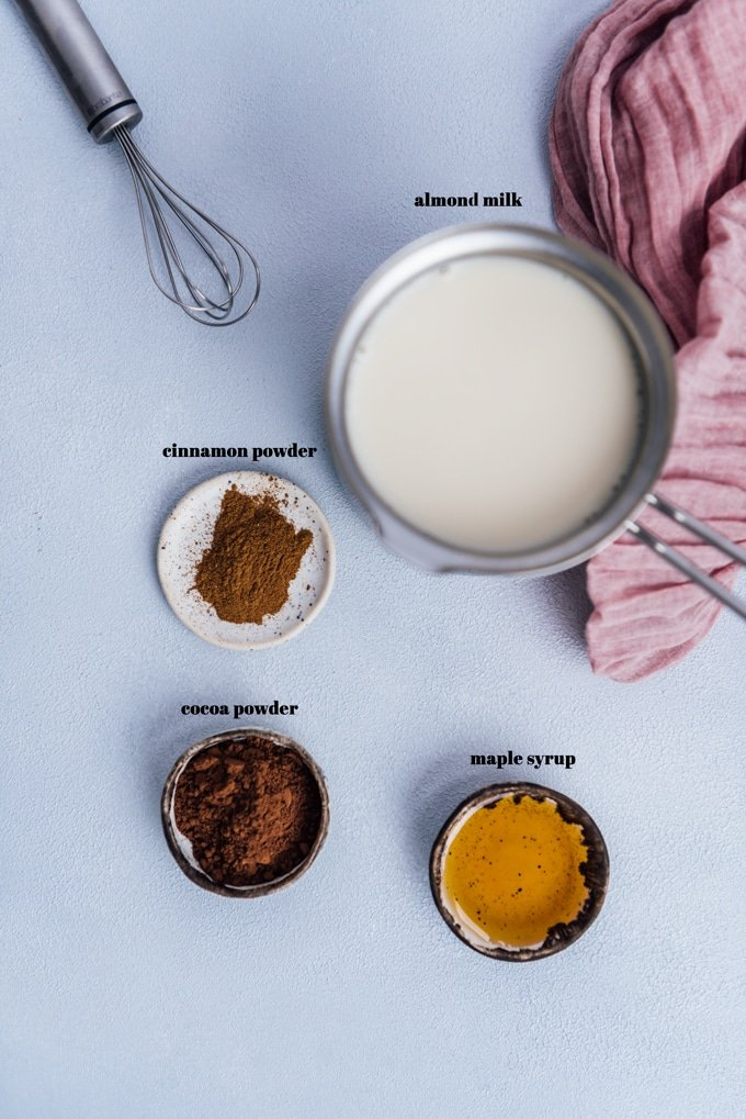 ingredients for hot chocolate with almond milk on a grey background