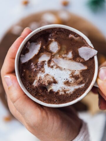 Holding a cup of almond milk hot chocolate topped with coconut oil and coconut flakes.