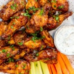 Baked wings with buffalo sauce served on a white plate with carrot and celery sticks.