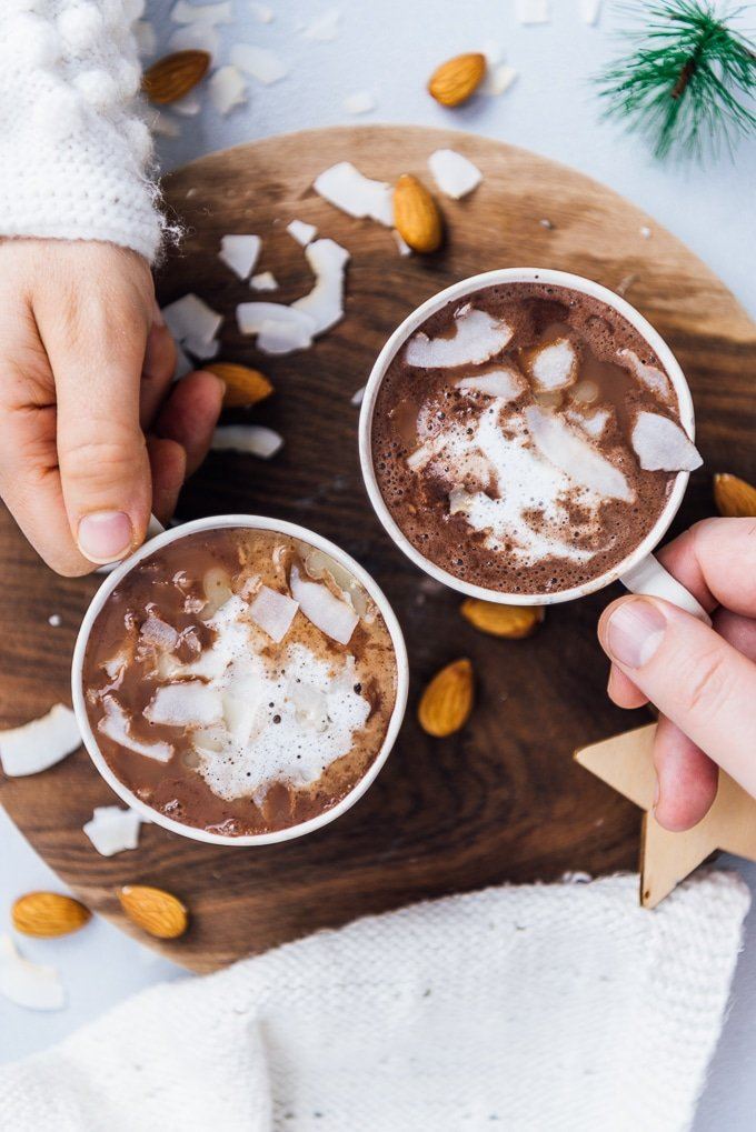 Hands holding cups with almond milk hot chocolate topped with coconut oil and coconut flakes