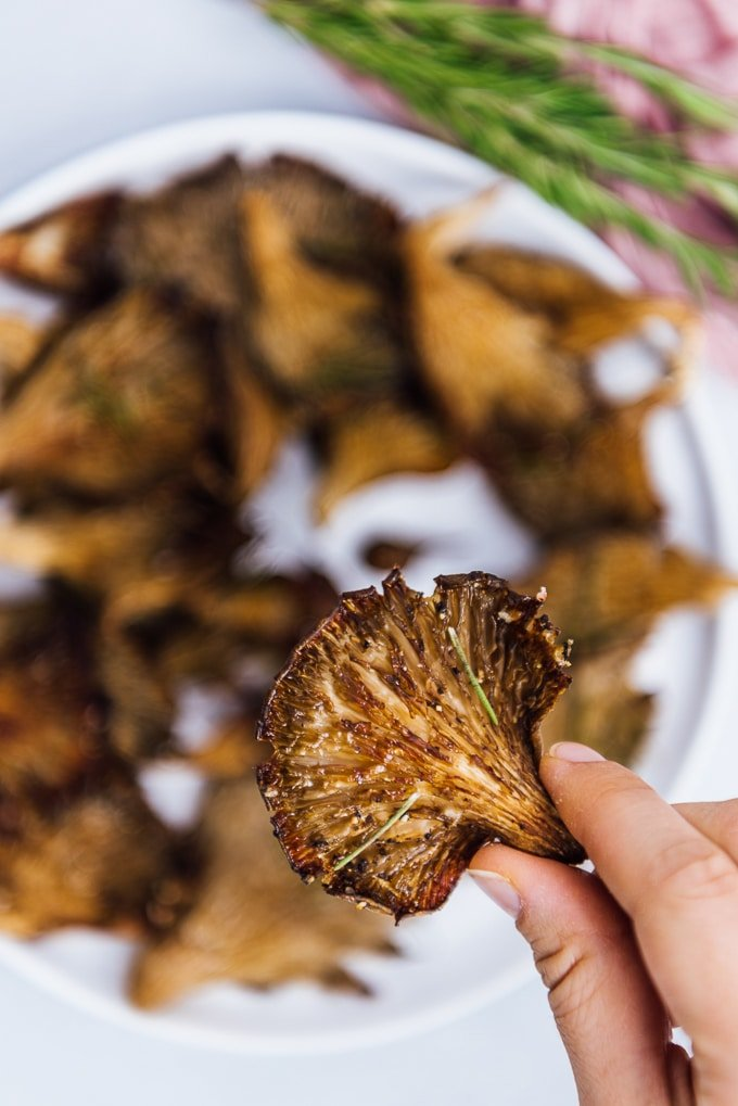 Holding a crispy oyster mushroom roasted in oven