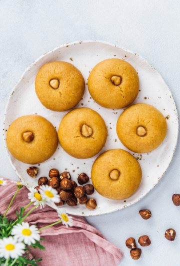 Semolina cookies soaked with sweet syrup on a ceramic plate accompanied by hazelnuts and spring flowers