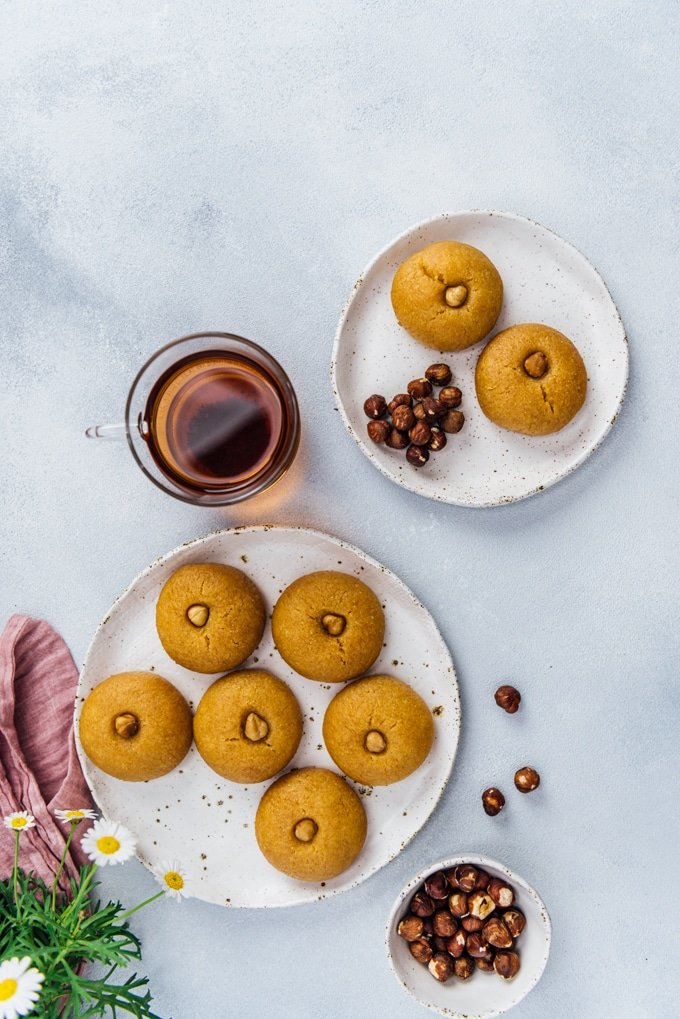 Semolina cookies soaked with sweet syrup on two ceramic plates accompanied by a cup of Turkish tea and hazelnuts