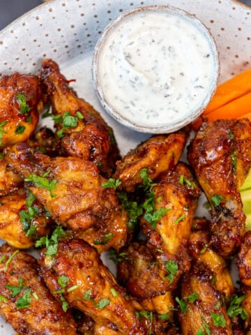 Spicy and crispy chicken wings served with a yogurt dip sauce, carrot and celery sticks on a white plate.