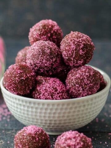 Chocolate truffles with biscuits coated with colored sugar in a white bowl on a dark background.