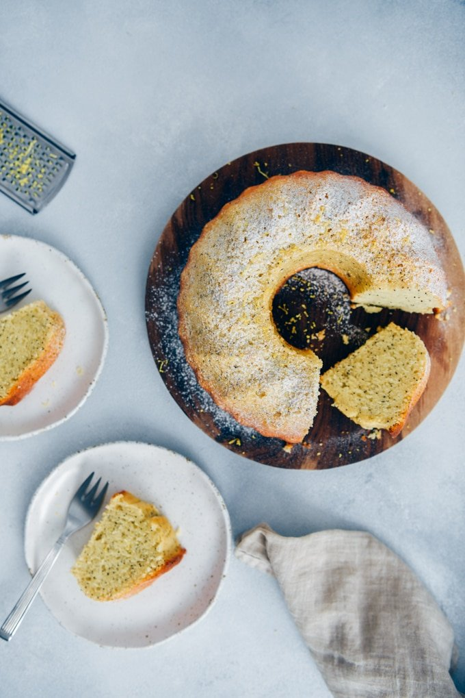 Moist lemon cake with poppy seeds on a wooden board and slices served on two plates