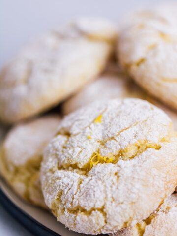 Lemon cake mix cookies stacked on a plate.