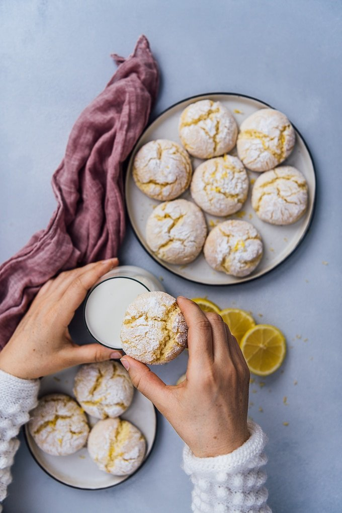 Woman's hands with white jumper holding a lemon cookie and a glass of milk.