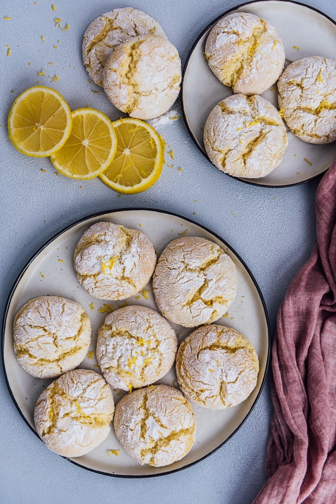 Lemon cookies served on two plates and accompanied by lemon slices.